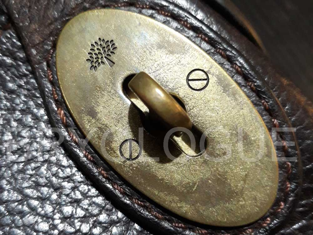 Detail of the Mulberry tree logo on the disc of the Mulberry postman's lock
