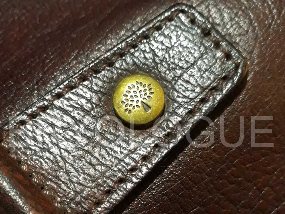 Close-up of the Mulberry stud, showing the Mulberry logo in this Ethan briefcase bag