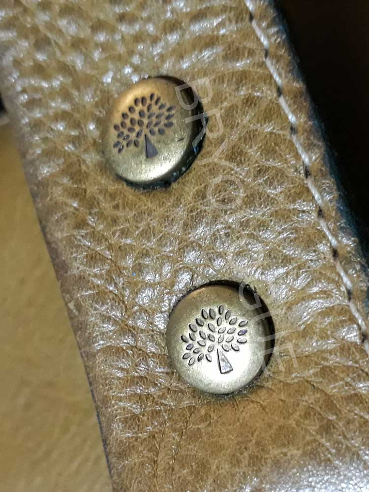 Detailed shot of the stud in a Mulberry Roxanne bag showing the clear Mulberry logo