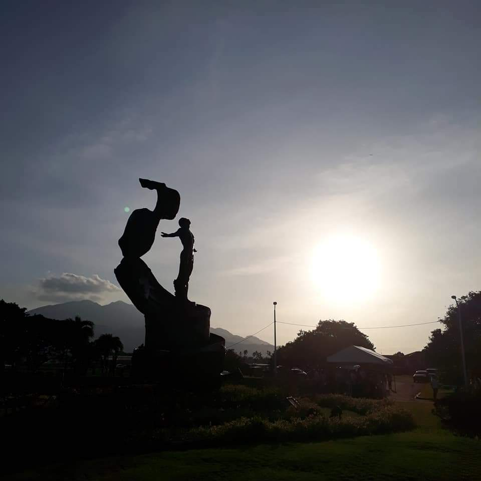 UPOU's Oblation silhouetted against the setting sun, with Mt. Makiling in the background